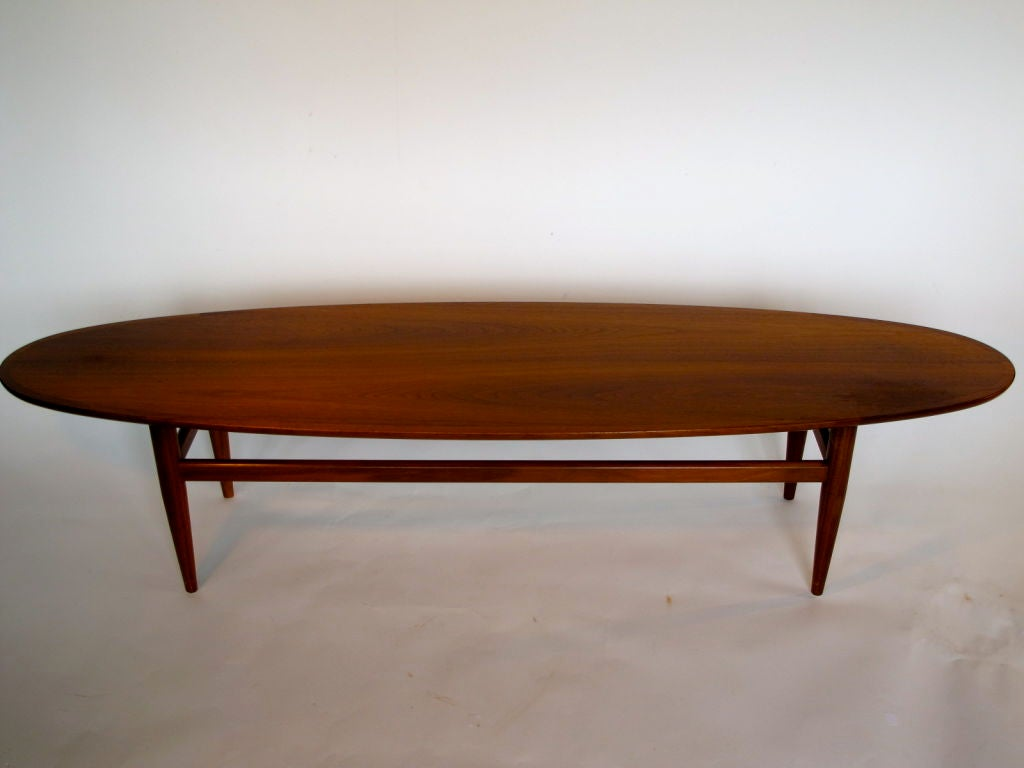 An elegant, modernist surfboard coffee table by Heritage in walnut.