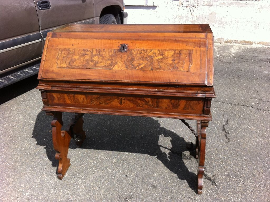 Italian fall front desk with burl wood inlay. With six drawers and two hidden storage areas. The top of this desk is 18th century, while the base, beautifully carved legs with wrought iron stretcher, is a 19th century restoration. A great looking