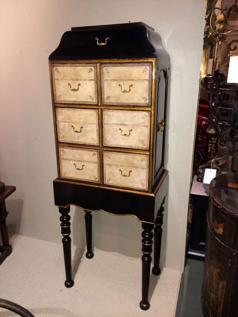 Beautifully made black lacquer and parcel-gilt cartonnier, or chest on stand, with tooled leather drawer fronts and gilt bronze mounts. In the French Regence style. A single drawer on top with six below. The chest lifts off of the base making it
