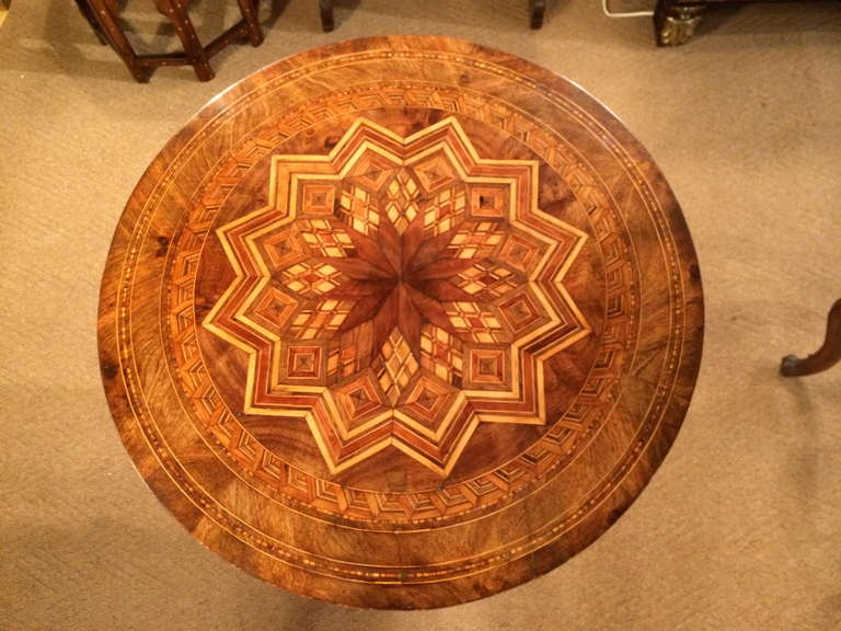 19th century Italian side or center table with elaborate marquetry top inlaid with walnut and various fruit woods, typical of Sorrento, Italy. The tripod base also inlaid with geometric patterns.