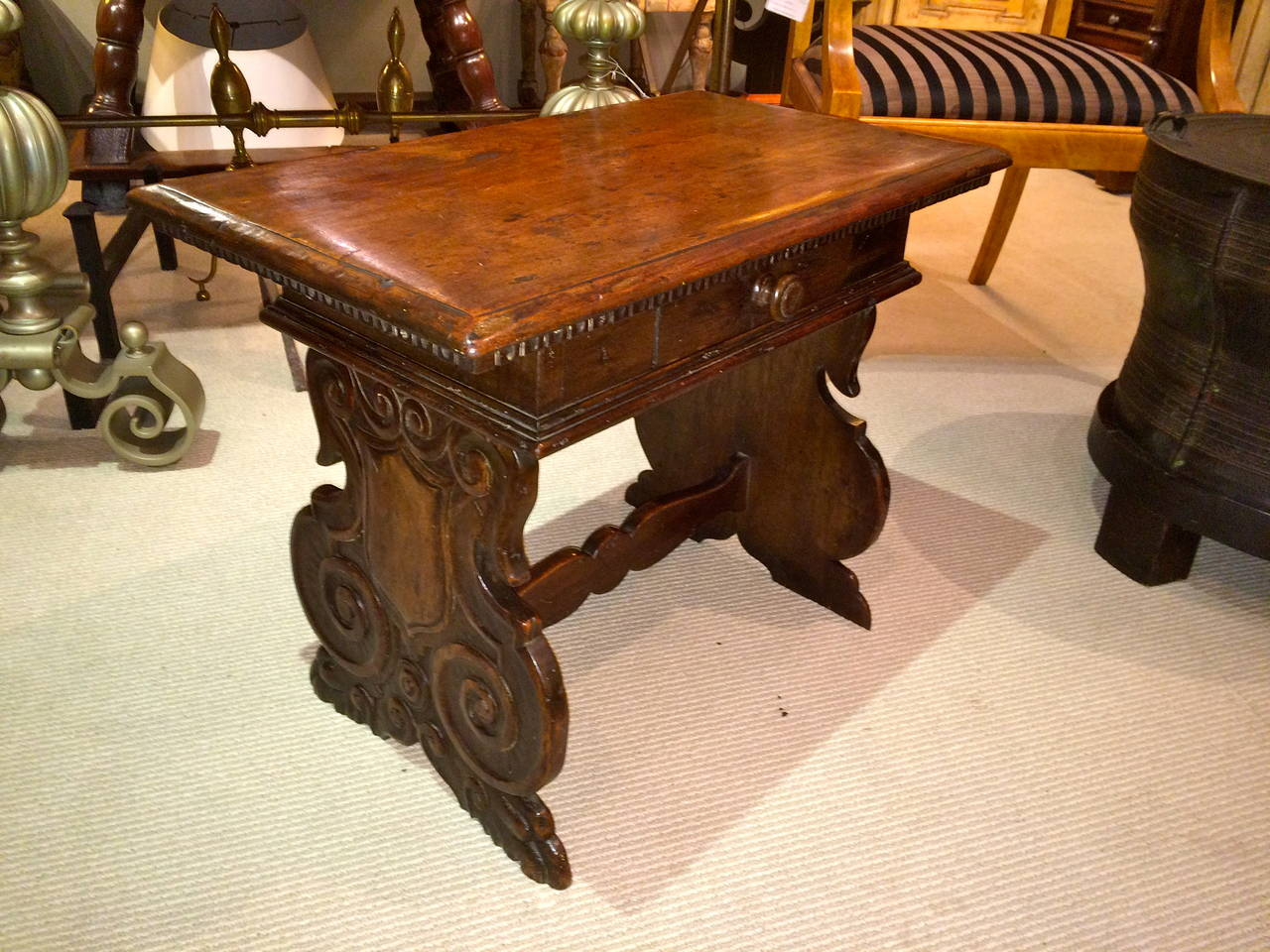 Handsome Italian Baroque style walnut side table with sides carved with scroll-work and paw feet. Single drawer, rich patina.