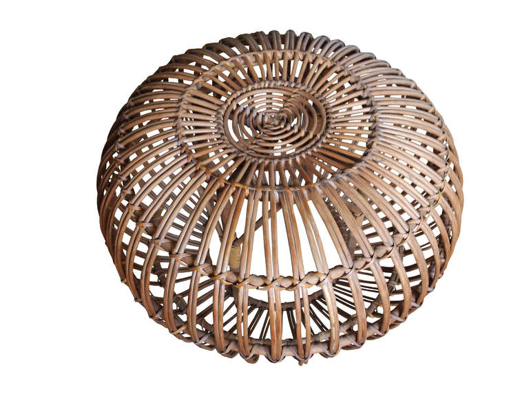 This rattan pouf can be used as a decorative side table or stool. The rattan is very strong and sturdy and is in excellent condition.