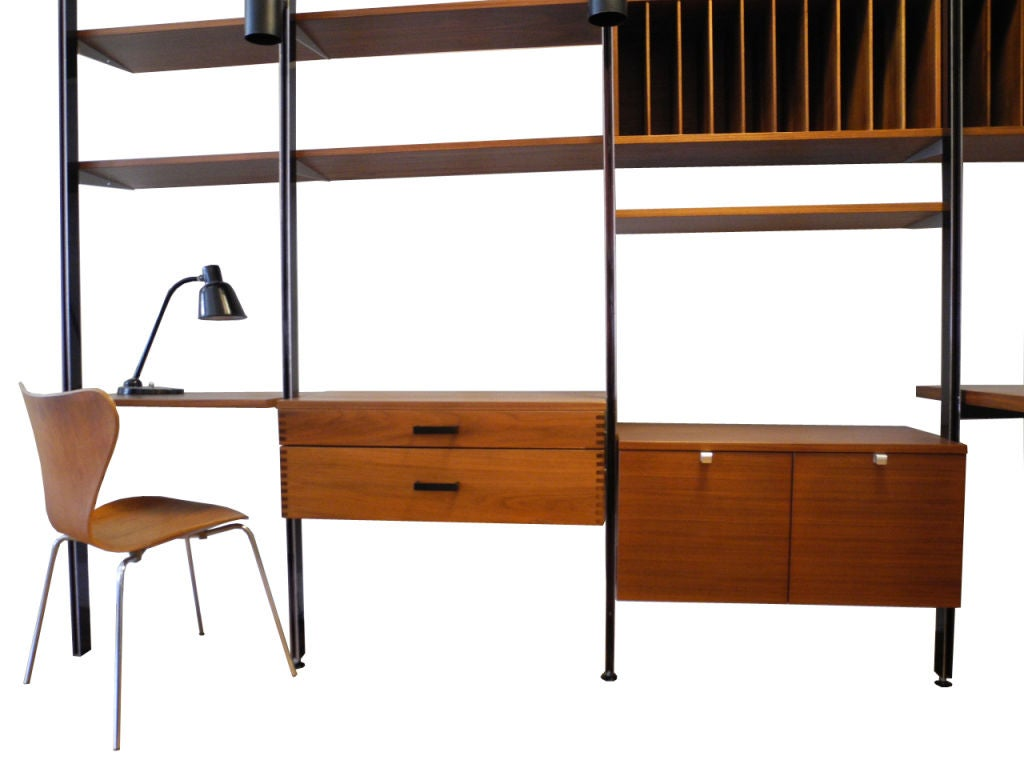 This is a super handsome walnut wall unit designed by George Nelson. It consists of 13 shelves, 1 double file cabinet, 1 file cabinet with drawers, 1 table/desk, 3 separate drawers (one not shown), a pencil desk, 6 poles, 3 lamps and two shelves