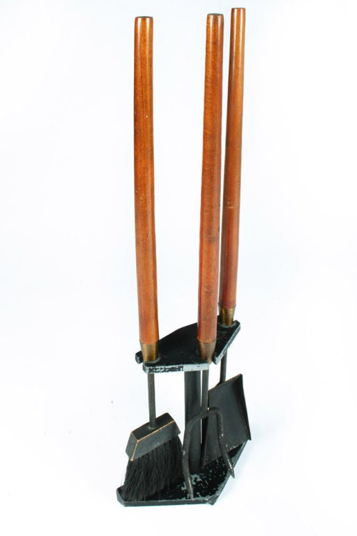 A set of fireplace tools comprised of a shovel, poker and broom each with long walnut handles and wrought iron tools held on an integral triangular wrought iron base. By Seymor Manufacturing Company, American, circa 1950s.