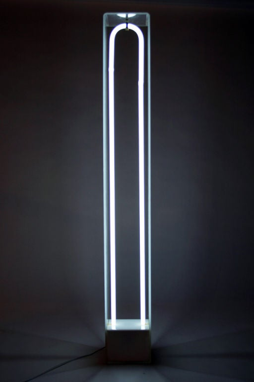 A fantastic light sculpture comprising an elongated U-shaped white neon tube held within a three-sided Plexiglas frame mounted on a painted steel base. Sproat designed a series of these in the late 1960s all with different color neon tubing. A