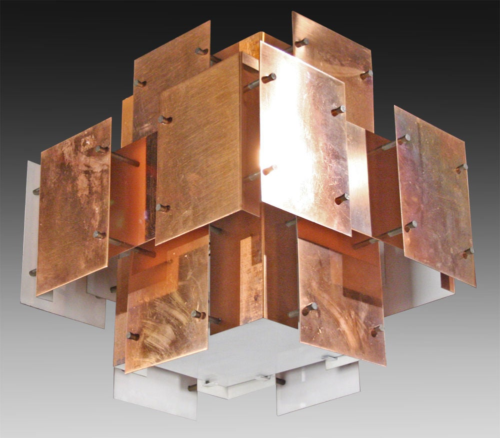 An architectural rectangular chandelier consisting of a three dimensional composition of 'floating' copper panels each separated and attached with blackened metal posts and cone studs. The fixture is fitted with the original black enameled stem and
