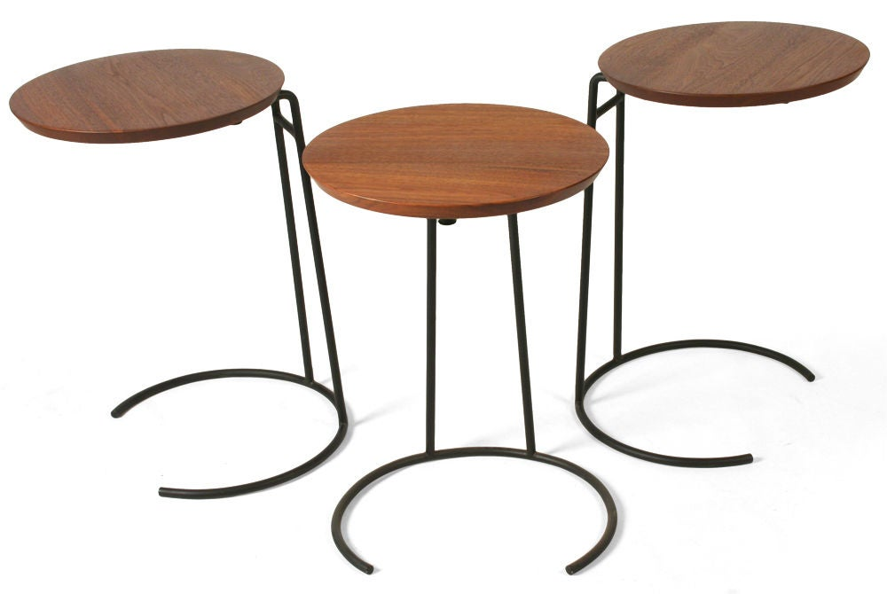A clever set of stacking tables comprising circular knife-edge tops cantilevered on black enameled wrought iron bases. Model T. 710. With partial maker's label to the base. Designed by Jens Risom. American, circa 1950.