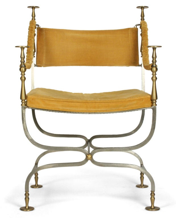 A savonarola style accent chair with velvet upholstered backrest, seat and arms in satin steel and turned brass fittings to the arms and feet.  Italian, circa 1960.<br />