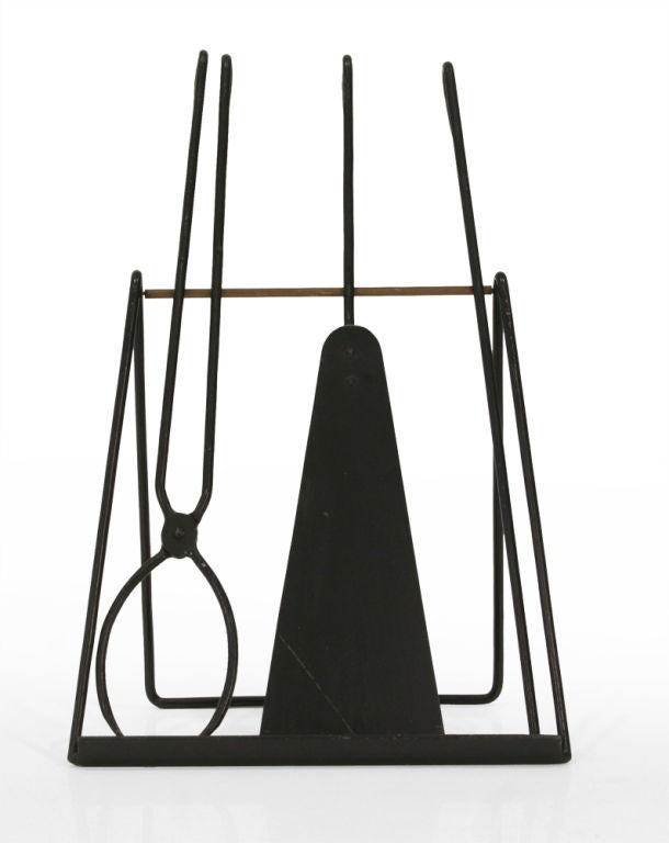A Modernist set of three fireplace tools in wrought iron with looped handles all resting on a easel form wrought iron and brass stand. Made for Illums Bohlighus. Danish, circa 1950.