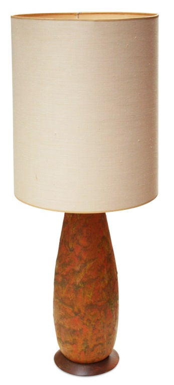 A beautiful ceramic table lamp with a thick lava glaze in vibrant colors of orange, yellow and swirls of olive green; the body in a slender, elongated bullet form resting on a circular wooden base. After Fantoni, Italian, 1960.