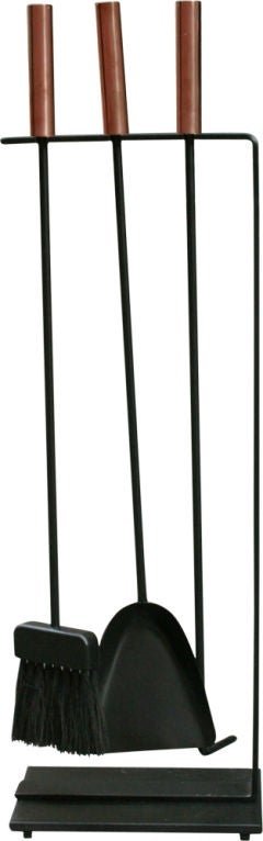 A set of fireplace tools consisting of three instruments with copper cylindrical handles supported by an integral freestanding rack in wrought iron. Manufactured by Pilgrim, American, circa 1950.