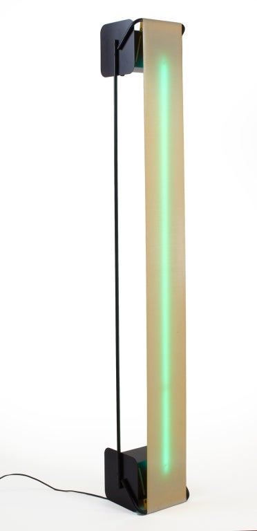 An avant garde light sculpture with a functional uplight torchiere. A single vertical blue green neon tube with a flexible webbed plastic diffuser, mounted in a minimalist black enameled steel frame. After Rudi Stern. American, circa 1980.