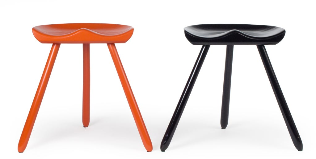 Milking stools with sculpted seats supported on three legs; one in orange and one in black lacquer. After a design by Mogens Lassen. Danish, circa 1940.