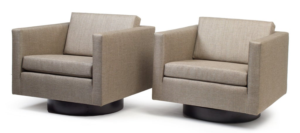 A pair of low conversational swivel lounge chairs in cube form raised on round ebonized bases. By Harvey Probber. American, circa 1950. COM.