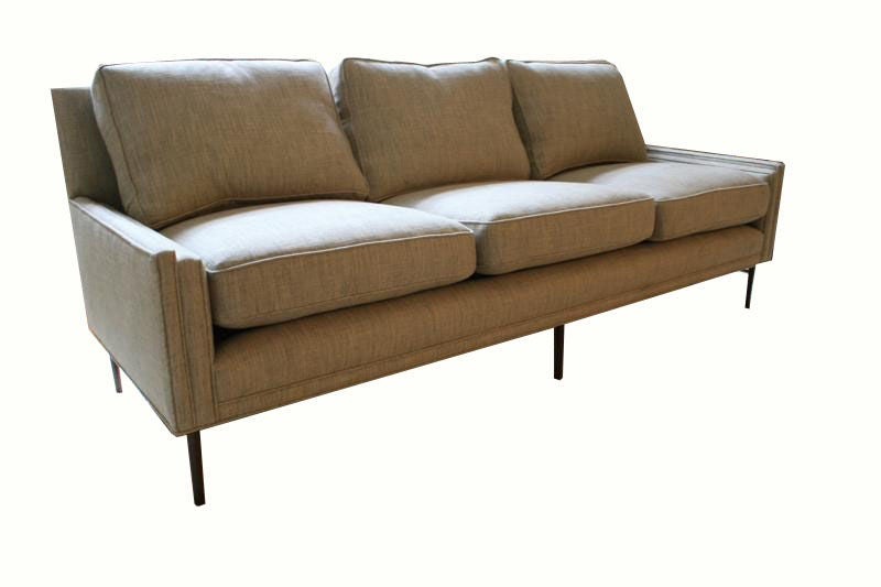 Mn Originals stepped arm detail three-seat sofa. Natural feather and down loose cushions over upholstered hardwood frame. Solid walnut tapered hand turned legs with outside legs detailed with brass stretchers.  COM requirements: 20 yards.  5%