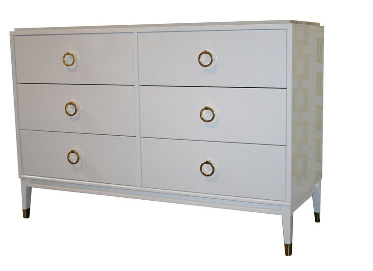 Six-drawer lacquered marble top dresser. Six equal sized drawers are fitted with solid brass ring pulls. Solid apron base with tapered legs that are detailed with polished brass sabots. Top surface is an inset polished marble top. Sabots shown not