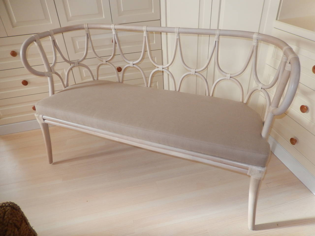 A curvaceous bentwood settee/bench upholstered in a stone linen fabric. The bentwood has a bamboo strapping above every loop.Stone wash on wood.