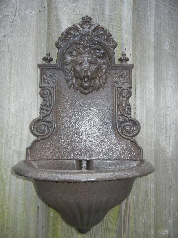 A cast iron water fountain or planter, showing excellent detail, especially on the lion head, powder coated bronze finish for out doors or in.