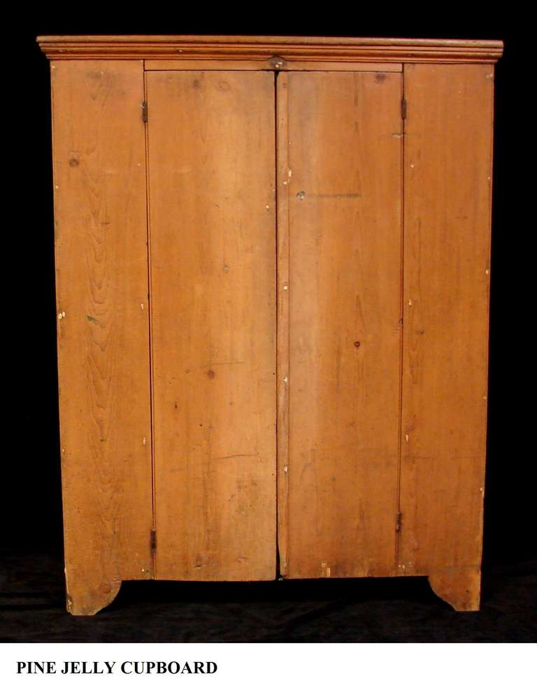 An antique Americana Pine wood jelly cupboard. Original milk stain paint.  Origin: Lancaster - 19th Century Pennsylvania Pine Jelly Cupboard For Sale At 1stdibs