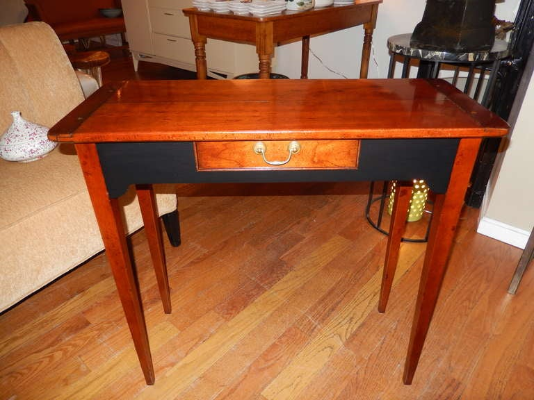 A modern version of the Federal period furniture, elegant tapered legs, one pull-out drawer with original brass hardware. The front and back have a slight cut-out with an ebony finish. Probably American made.