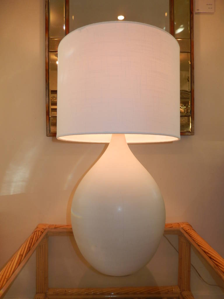 A bulbous form hand-thrown and hand studio crafted white bisque pottery table  lamp. Three way switch, clear cord, new linen shade.Measures 20 inches to the socket and 27 inches to the top of the shade.