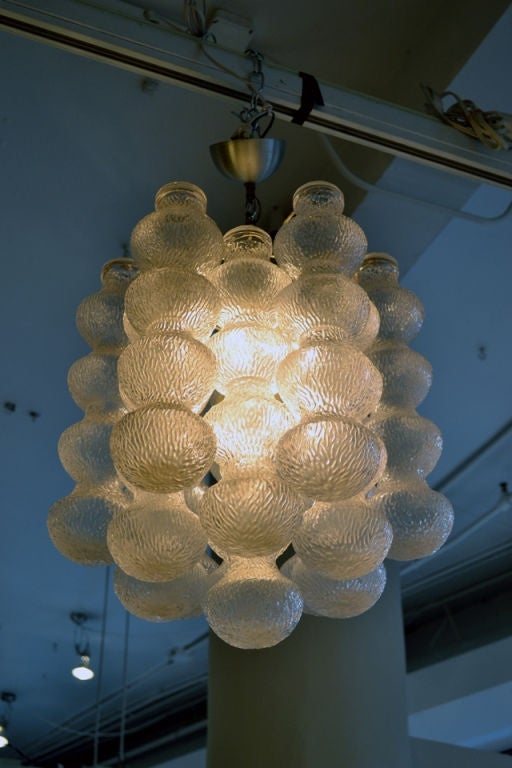 A fine chandelier comprised of 14 Murano hour glass designed cylinders, interlocking to form a very harmonious lamp.