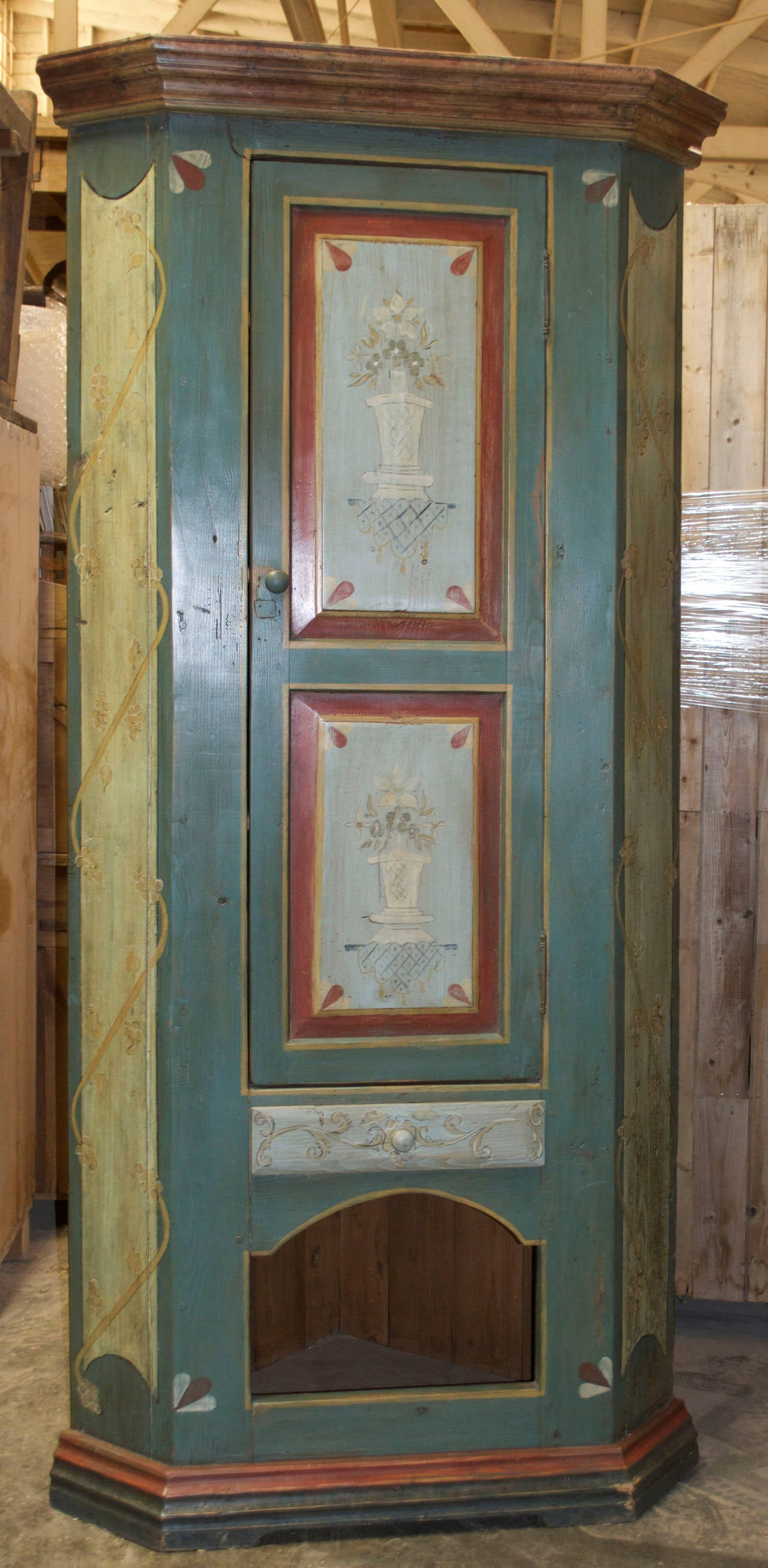 Masterfully painted corner cabinet with two doors, a drawer and a cubby-hole below.