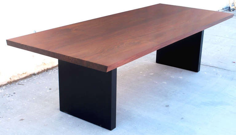 This table has a spectacular design! The tabletop consists of two solid, bookmatched, walnut slabs