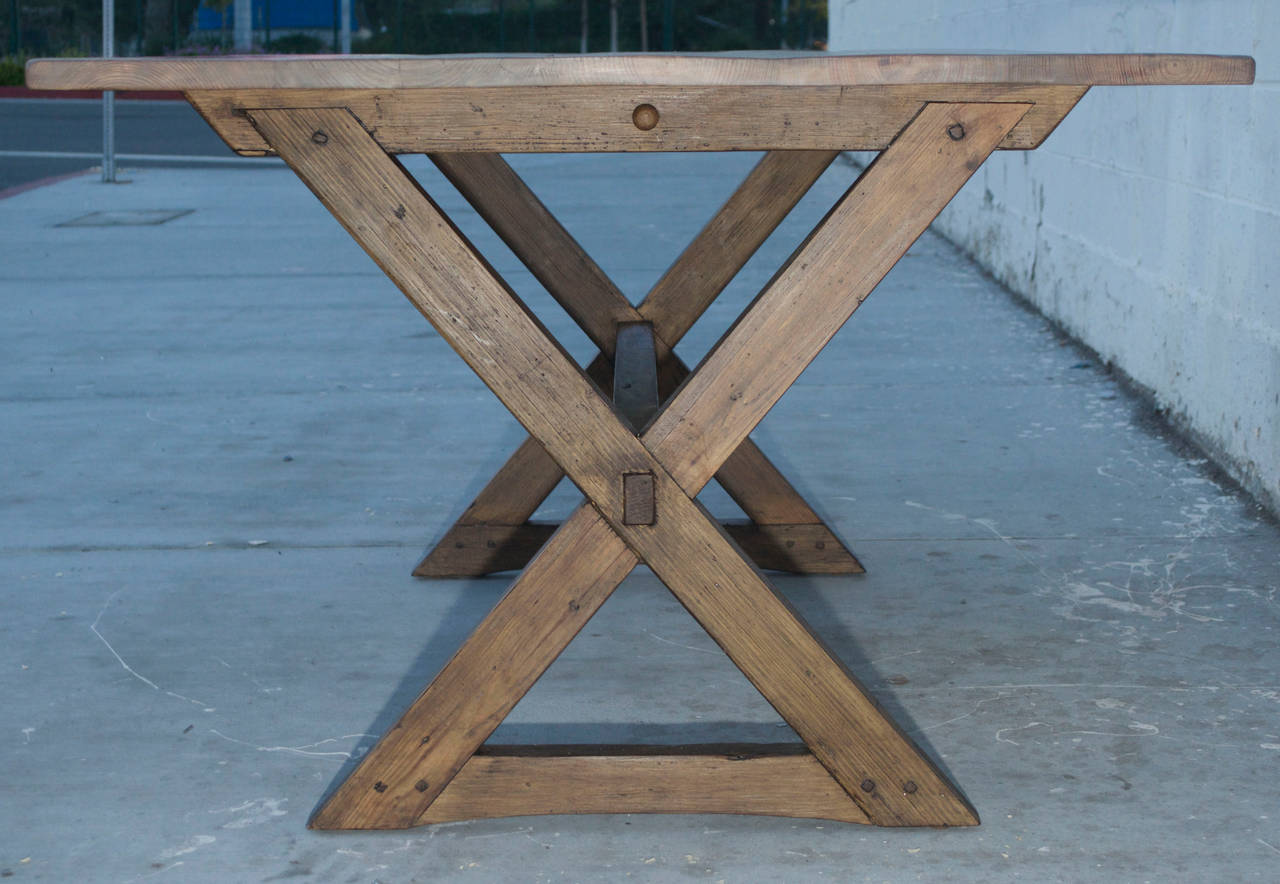 This pine trestle table is made from solid, reclaimed heart-pine planking. Lots of character and charm! The top can be taken off the base by pulling out the round pin at the top center of each leg, right under the table top.  Matching benches are