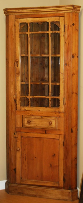 Charming corner cabinet. Has nicely carved details in arched upper cabinet with two scalloped shelves behind a door with glazed panels and decoratively carved features. Below is a single drawer and a lower compartment with a single shelf behind a