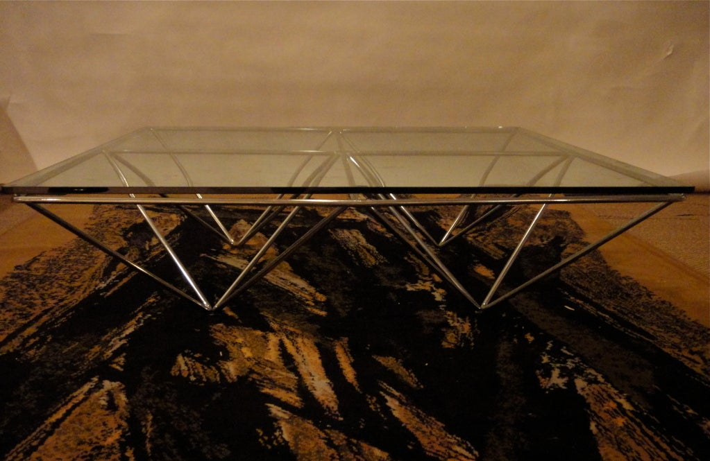 Coffee table with chromed steel bars that form a diamond pattern and support a square glass top