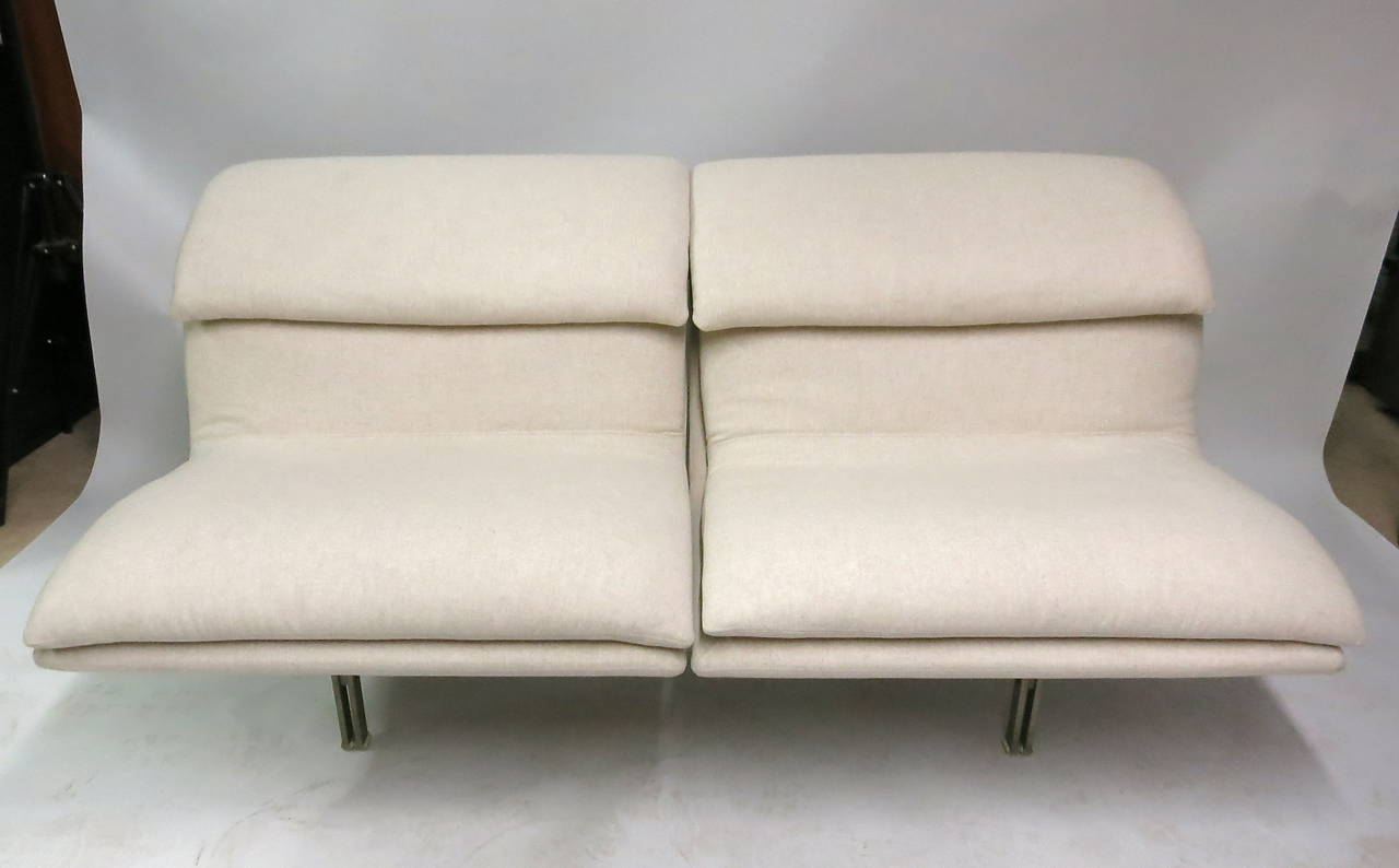 Pair of love seats with a frame made of solid brushed steel that supports the entire sofa. Each sofa has been recently upholstered with vintage cotton fabric. The manufacturer's labels appear on the back side of the frames single front stretcher.