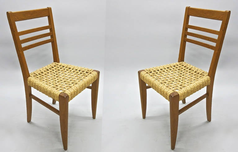 A pair of chairs with a solid oak frame and braided rope seats designed and documented by Adrien Audoux and Frida Minet in 1950. Documented in issue 54 of Revue D'aujourd- hui, 1950.