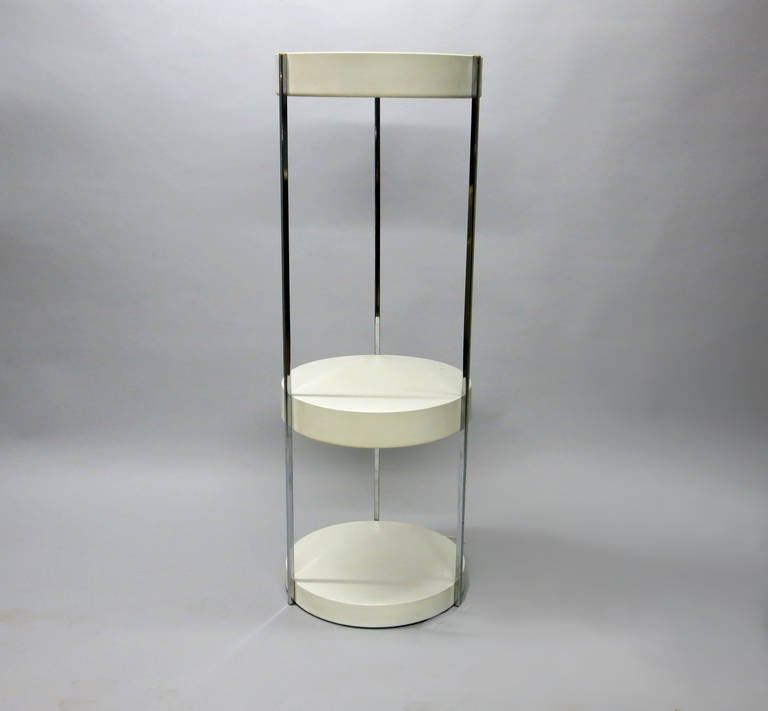 Display stand that also doubles as a floor lamp, has three round shelves in white enameled metal that are vertically connected by three chrome post supports. The top two shelves have florescent lights that illuminate the shelf below.