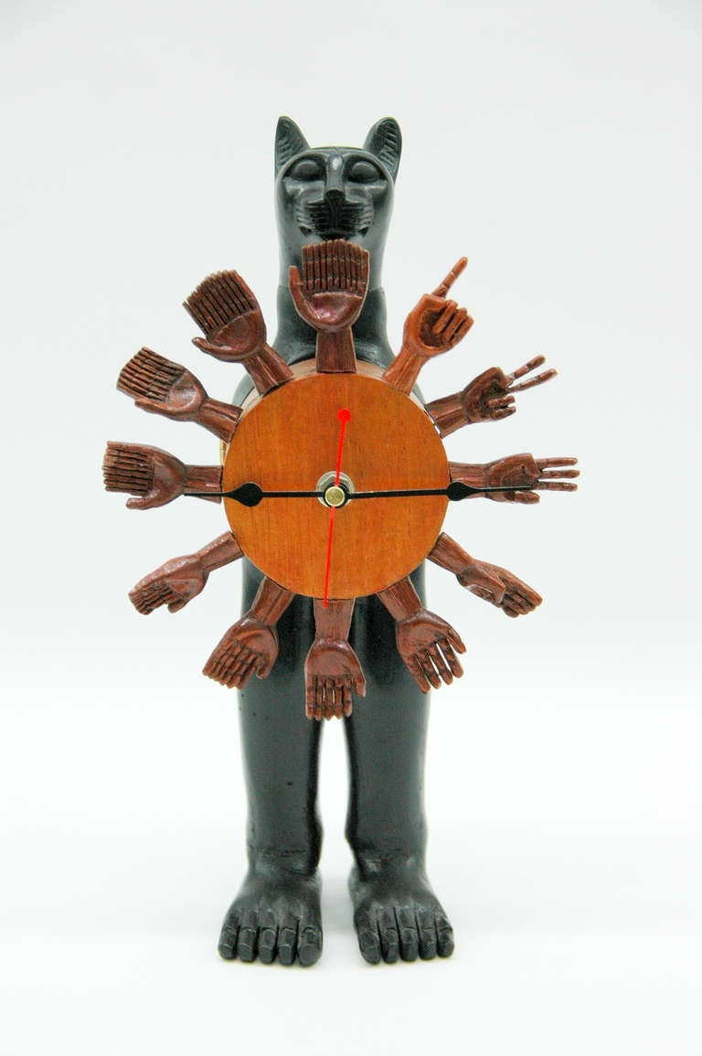 A very unusual table clock designed by Pedro Friedeberg featuring a wooden black Egyptian cat with the clock on its torso. The clock is also made of wood, with hands as the numbers from one to twelve. The battery and time can easily be changed, the
