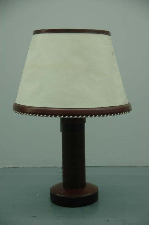 A rare Hermes desk/table lamp designed by Paul Dupré-Lafon formed of circular sections of stacked leather on a quilted leather base retaining original hardware and original parchment hide (vellum?) shade with leather trim and