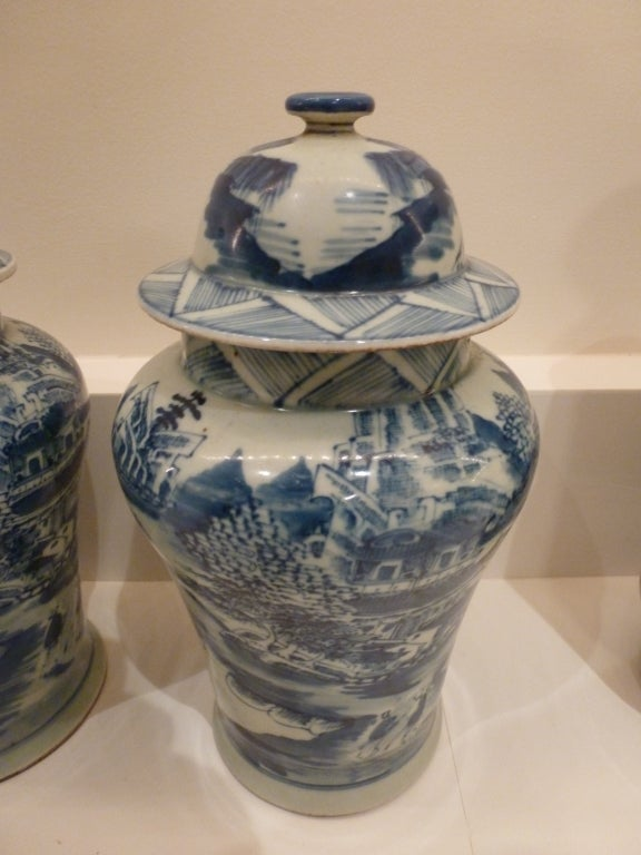 A fine pair of lidded jars or vases with traditional landscape scenes.