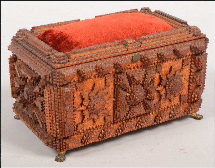 A handcrafted dresser or jewelry box with hinged pincushion lid and applied, chip-carved decoration. The interior with framed mirror on underside of lid and papered in a purple and white printed pattern. The box rests on four cast brass lion paw