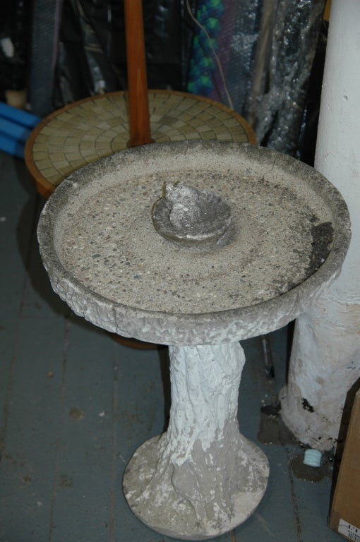 The basin circular and shallow with raised rim around the edge and a miniature basin in center (perhaps for bird feed?) both removable basins resting on a naturalistic 'trunk' pedestal column that flares at base for stability.