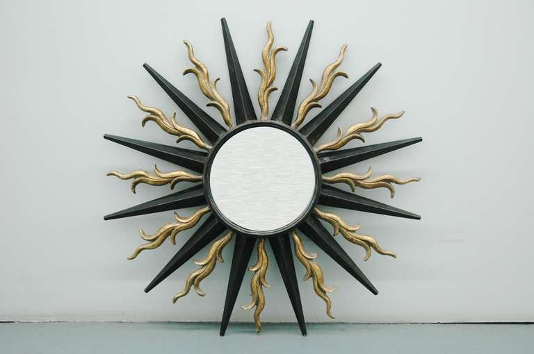 A large wall-mounted sunburst mirror in the style of Gilbert Poillerat. Poillerat was a French designer who mostly worked in wrought iron and is associated with the Art Deco period reaching into the 1930s and 1940s. He received his training at École
