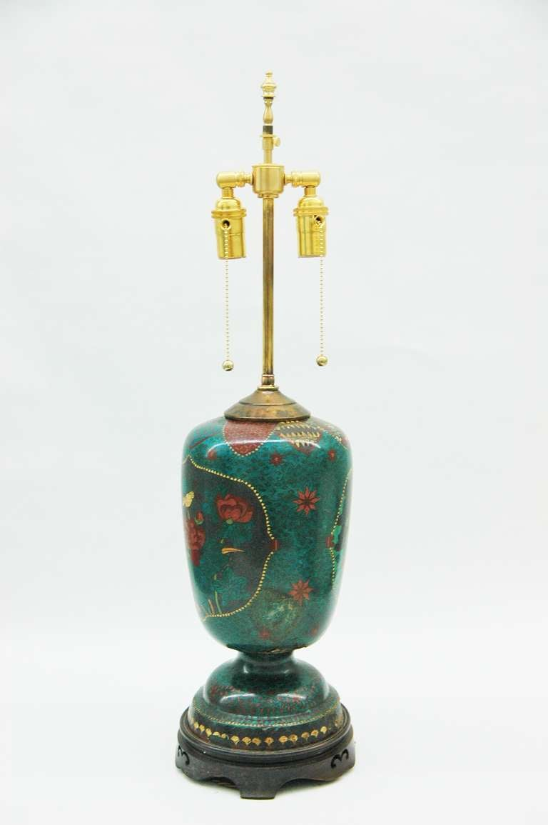 An intricately decorated navy blue and turquoise table lamp with birds and flowers illustrations done in cloisonné on a circular stepped pedestal base on a carved and turned teak wood base. 