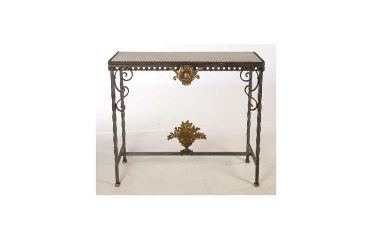A console table with iron and bronze details with a white marble top, the iron frame with a gilded bronze medallion at the top rail above a gilded bronze applique of flowers in a vase sitting on the stretcher.