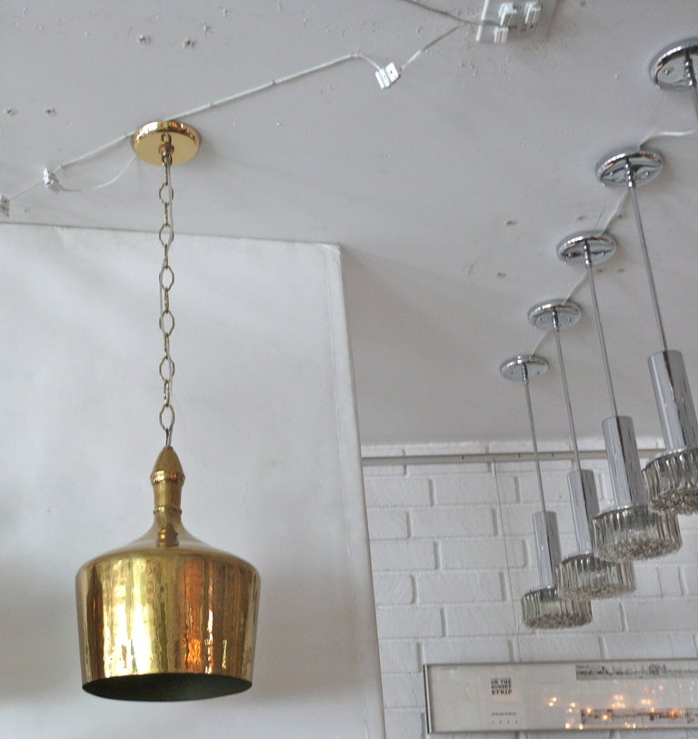 Gorgeous pair of brass jug pendants. Jug shape with slender neck which extends to chain. Heavy polished brass finish with light hammered detail on surface. Nice medium sized scale. Perfect pair for kitchen island. Sold individually. Professionally