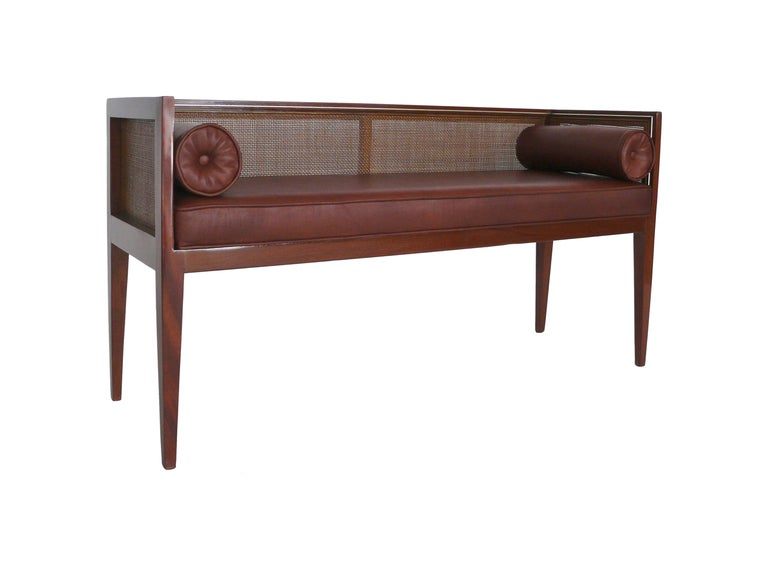 Stunning walnut bench with newly upholstered bench seat and  bolster pillows.  Leather is a rich shade of maroon. Canning on the backrest and sides with a thin silver detail lining the edge.  Bench rests on beautiful tapered legs.  A simple yet