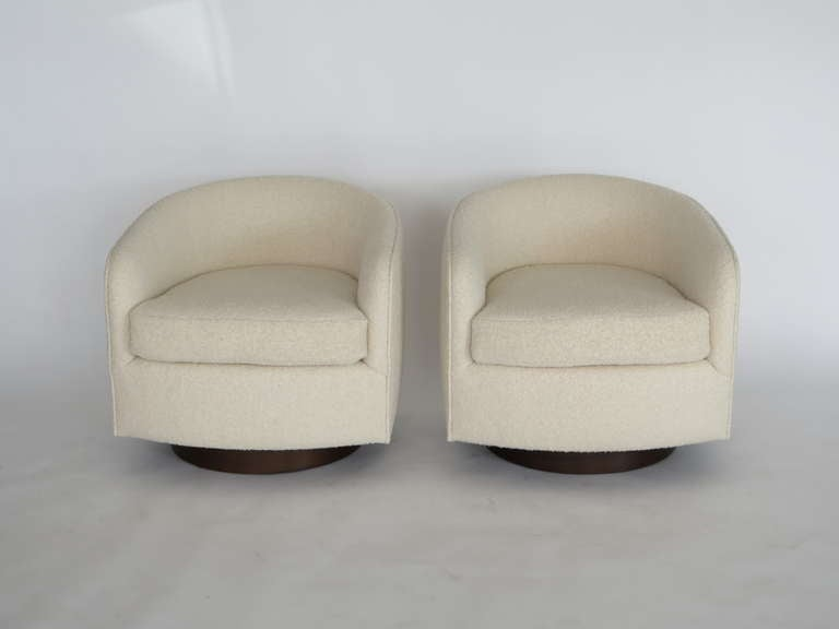 Newly produced pair of swivel chairs in the style of Milo Baughman. Creamy white wool boucle with medium walnut wood swivel base. Extremely comfortable and functional with sleek modern design. Can be COM or COL.