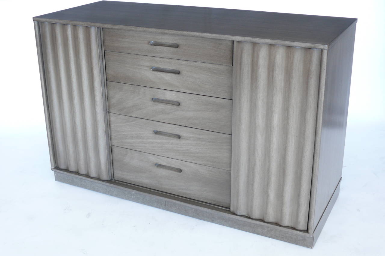 Dunbar cabinet with corrugated wood front. Beautiful, well designed piece, corrugated slide wood doors to hide center drawers and then reveal side shelving. Base is leather wrapped. Original Dunbar tag. Newly refinished in a smokey gray. Perfect for