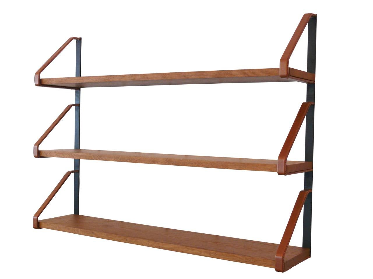 """Handsome oak and leather bookshelf in the style of Jacques Adnet. Newly produced after a vintage Adnet bookshelf. Custom iron frame with saddle leather wrapped brackets and signature contrast stitching. 1"""" thick oak shelves and brass hardware."""