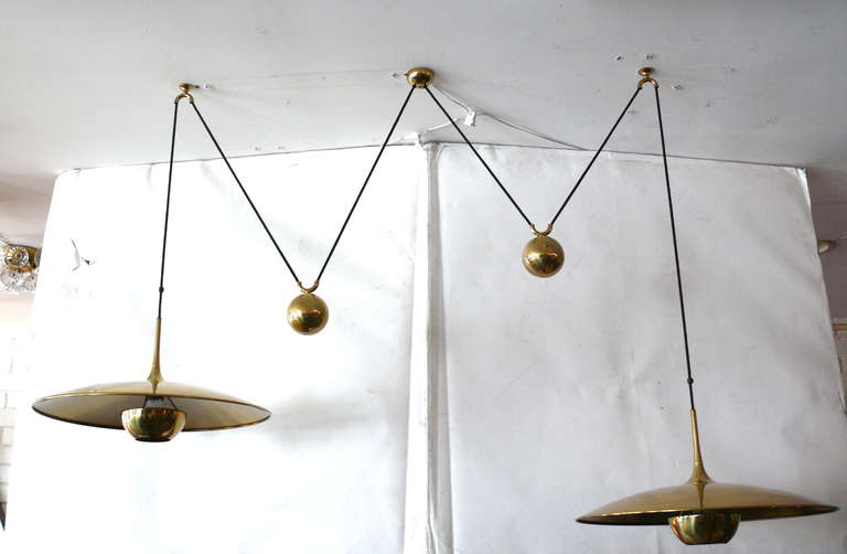 Fantastic double counter balance pendants by Florian Schulz. Two brass pendants suspended with their own brass ball counter balance. One canopy supports both pendants. Each light is adjustable in height without affecting the other. Great design.