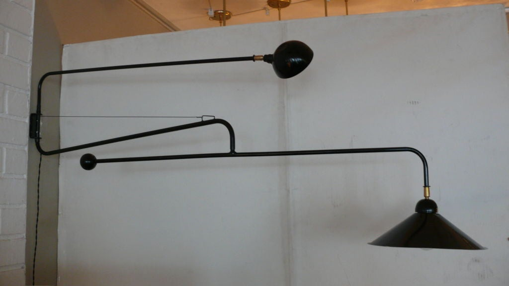 Large scale exquisite black steel double arm articulating wall sconce. Both arms and heads fully pivot and rotate with positional brass adjustments at the shades, the second arm with weighted ball. Multiple available and priced individually.