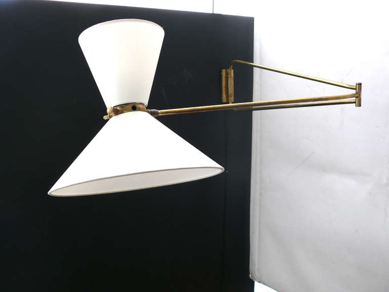Beautiful wall sconce by Pierre Guariche. Sconce has two light sources to provide up lighting and down lighting. Articulating sconce with full 180 degree movement. Arm can extend or lay close to the wall. Original brass hardware with great patina.